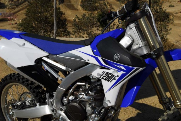 "The YZ250F's slim and flat layout adds to its ergonomic excellence. Note the lack of a fuel cap on the ""tank"". The 2.1-gallon fuel cell is actually located low between the YZ's aluminum frame spars and toward the center of the seat. The fuel filler is accessed through and easy-to-remove section at the very front of the seat."