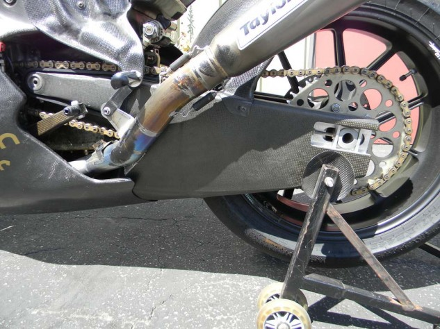 Testing revealed the original carbon swingarm would flex torsionally under load, causing massive front chatter. This, the fifth iteration of the swingarm, features a substantial cross-section of material in order to spread the torsional load over a large surface.