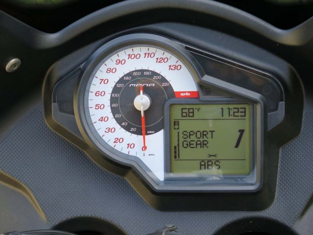 Hold the selector button down for 3 seconds, and you will be in Sport Gear mode, whereupon you have a 7-speed seamless clutchless gearbox you can shift with either your left finger and thumb, or left foot. Sequential shift lights across the top tell you when. Ambient temp gauge is accurate, there's a clock, a lap timer, a pessimistic fuel mileage indicator, et cetera …