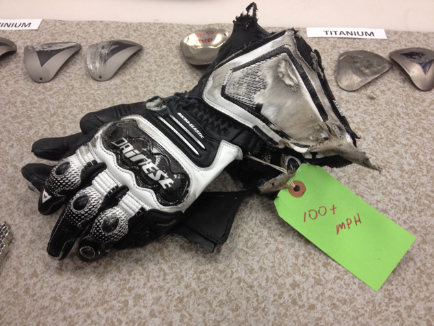 As any respectable safety company would, Dainese inspects as much of its crashed products so it can to see how they perform in the real world. Here, gloves worn – and crashed – during the Daytona 200 are inspected to see if they performed as designed. They did. Note the titanium plates in the background seen on jackets, pants and suits. These also get inspected and evaluated after a crash.