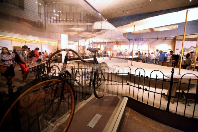 A Wright Brothers-manufactured bicycle sits beside the original Wright Flyer.