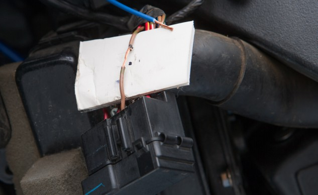 The insulation has been removed from the wire from which you plan on stealing a little power. The cardboard protects the rest of the wiring harness from inadvertent damage from the soldering iron.