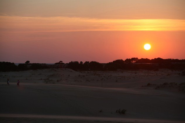 The sun sets over the sand dunes at Jockey's Ridge State Park. The Wright brothers chose North Carolina's Outer Banks as the place for their experiments because the dunes provided a place to launch their gliders and the sand was soft for landings.