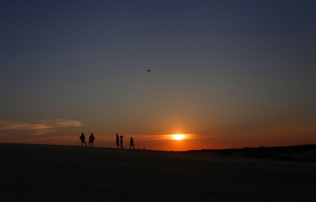 People launch kites as the sun sets at Jockey's Ridge State Park.