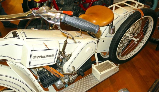 The recreation of a 1921 German Mars, which employed a 1000cc opposed-Twin from Maybach. The lever below the seat shifts from low to high drive chain. Rear wheel had two sprockets.
