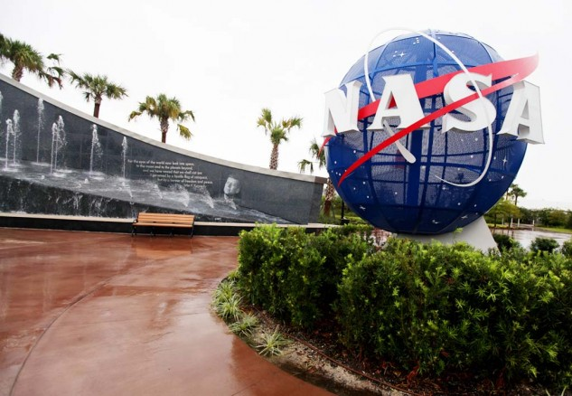 "The famous NASA ""meatball"" logo in front of Kennedy's words ""For the eyes of the world now look into space, to the moon and to the planets beyond..."""