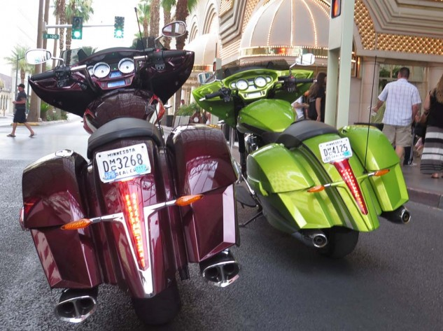 "The Ness Midnight Cherry bike on the left has Victory's louder Tri-Oval Exhaust and medium apes; the Plasma Lime version on the right is bone stock. Note the color-matched dashboards and ""close-outs"" that cover the bag mounting hardware and seams."