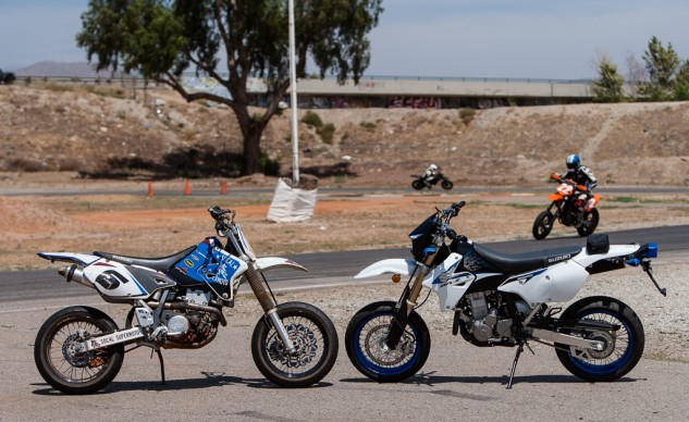 Each school bike (left) starts life as a standard Suzuki DR-Z400SM (right). Better rubber and brakes are added, as well as an exhaust, graphics kit, and assorted protective bits. Performance is noticeably better than the stock bike, but still docile enough for a newer rider.