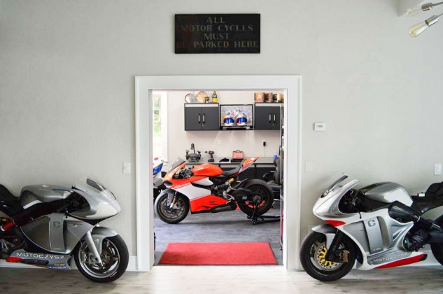 """While we don't have any pictures of the home he designed for Cindy Crawford, here's a glimpse at the entryway to Michael Czysz's garage. Original C1 prototype on the left, later version on the right, Ducati Superleggera in the middle. Sign reads: """"All Motorcycles Must Be Parked Here"""""""