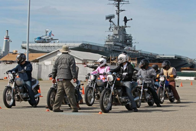 MSF RiderCoach Rob Kong leads a class through a counter-steering drill with the USS Hornet in the background.
