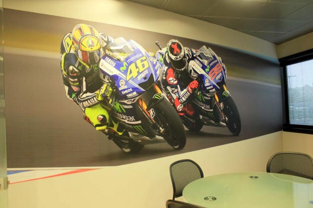 """Wall art. Jarvis tells us that Rossi is super analytical with his bike's setup. William Favero, Communications Manager of Yamaha Motor Racing, says VR46 would spend all day in the garage with his engineers and mechanics if he could. Jarvis believes Lorenzo has been less analytical in the past but is delving deeper into that aspect to make sure he is doing everything he can to remain competitive. Lorenzo's skills are so high, according to Favero, that he """"could ride a washing machine fast."""""""
