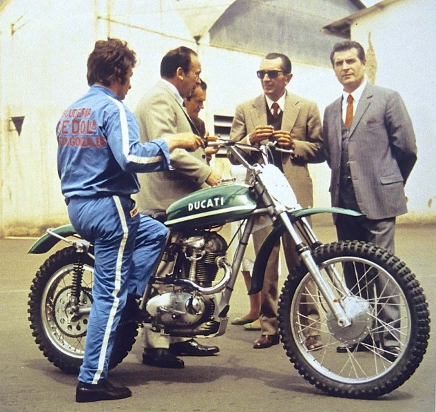 "The last iteration of the original Ducati Scrambler family was the 450 R/T, here in motocross trim for testing. The Doctor of Desmology himself, Fabio Taglioni (wearing shades),discusses the machine with the corporate chiefs. Longtime development rider/racer, Franco Farne, wears NCR race shop work clothes with the slogan ""Scuderia Speedy Gonzales."" The 450 had a desmo valvetrain and weighed 285 lbs wet."