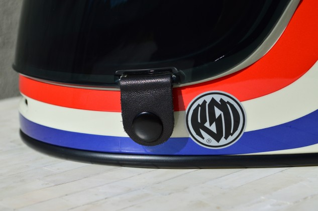 Bell's Magnefusion shield closure system is simply a leather tab with a magnet on the other side of that button, but it works surprisingly well at keeping the lid from popping up at speed. The tab makes it easy to open and close the visor with gloved hands.