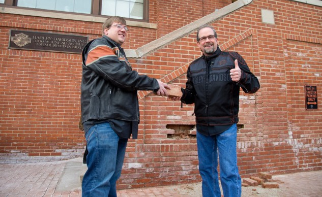 Bill Davidson, great-grandson of company co-founder William A. Davidson, right, hands a brick to Sturgis, S.D., Mayor Mark Carstensen after its removal from the historic Milwaukee headquarters.