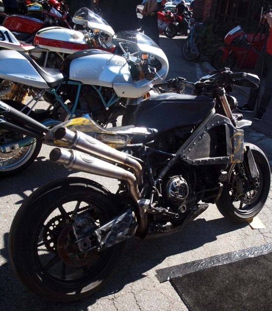 Mad Max meets semi-mad Roland Sands, bike designer extraordinaire, ripped his badass take on a Ducati and gave it the stressed and distressed cosmetic treatment. A Paul Smart edition Ducati lurks behind it. Built by Ducati in 2006, the PS1000LE commemorates Smart's victory at the Imola 200 in 1972, a major upset when he beat the legendary Agostini on his MV Agusta purpose-built racer. Smart's factory was basically a touring bike, a Gran Tourismo 750 aka GT750, the first with the famed Desmodromic engine.