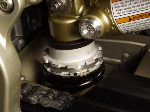 Here's a monoshock and its locking-ring spring preload adjuster. The shiny bit in the upper middle of the photo is the compression-damping adjusting screw. Note the S (soft) and H (hard) markings. Photo by Evans Brasfield.