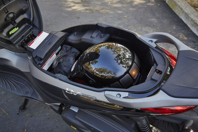 A front-hinging seat makes the storage compartment readily accessible. There's only room for one helmet, but note the little pouch underneath the seat itself (above the green sticker). That's a waterproof cover for the seat, another nice detail that helps separate the BV350 from the rest.