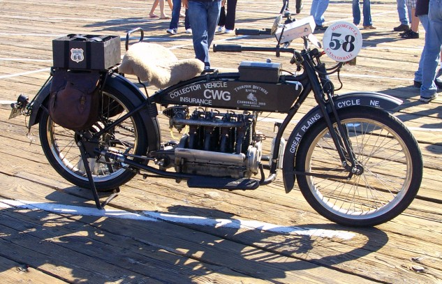 "Kris Thompson's 1915 Henderson Four ""rolling billboard"" that he rode in the 2010 Cannon Ball Run. For the 1915 model year Henderson offered the Model D and E with wheelbases of 65 and 58 inches, respectively. Standard bikes had a price tag of $295, the two-speed $325, a hefty sum at the time."