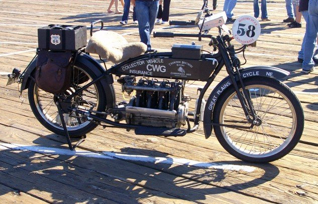 """Kris Thompson's 1915 Henderson Four """"rolling billboard"""" that he rode in the 2010 Cannon Ball Run. For the 1915 model year Henderson offered the Model D and E with wheelbases of 65 and 58 inches, respectively. Standard bikes had a price tag of $295, the two-speed $325, a hefty sum at the time."""