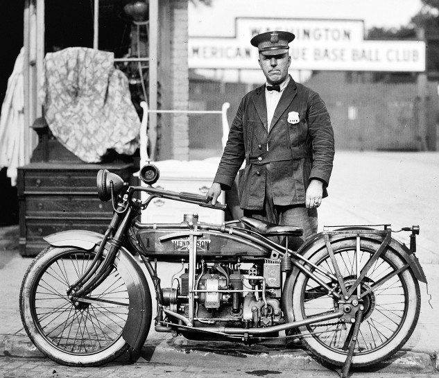 1922 photo taken in Washington D.C. shows a tough looking motor officer and his Henderson Four. Sign in background is for the Washington American League Baseball Club, now the Minnesota Twins. Police departments often compared Harley-Davidson, Indian, Ace and Henderson machines, however the latter four-cylinder bikes were much more expensive, if more comfortable.