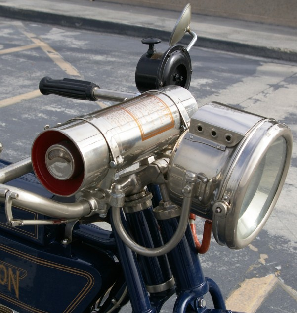 Works of techno-art in their own right, the Henderson's acetylene-powered headlamp and canister that contains its fuel, a mixture of calcium carbide and water. First discovered in 1892, acetylene soon powered lighting for lighthouses, miner's caps, bicycles and cars. Seen here also mounted on the handlebar is a large horn sometimes mistaken for a siren. Just press down on the plunger to get tooting.