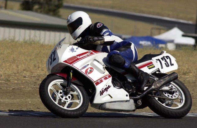 Denise Howard shows off her old Ninja's battle scars at Sonoma Raceway, 2002. Photo by Gary Rather.