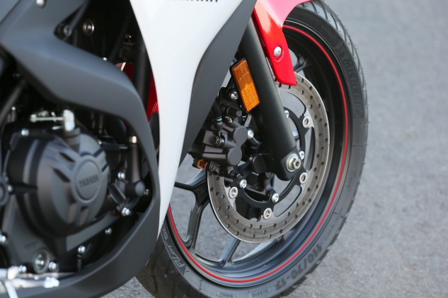 A single 298mm disc up front does the bulk of the stopping duties with its Akebono two-piston caliper. Note also the 10-spoke cast aluminum wheel and Michelin Pilot Street rubber.