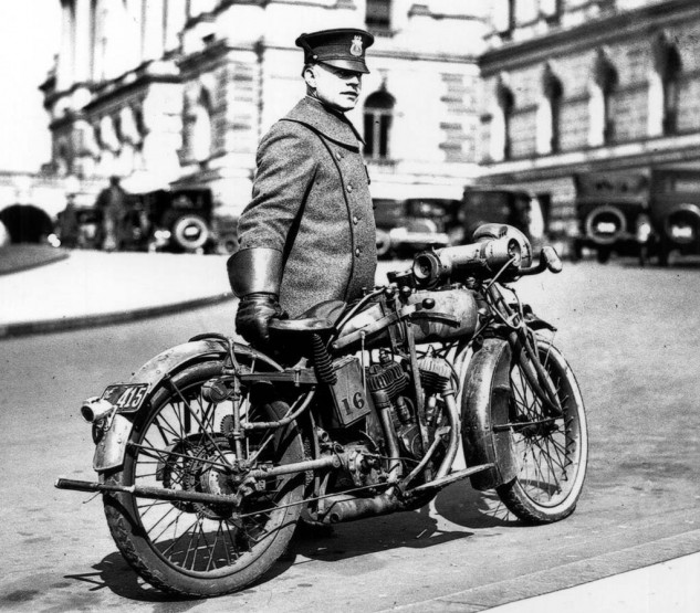 What appears to be a 1918 Indian Powerplus serves as a member of the Washington, D.C. police department and stands at the ready along with its gauntlet-wearing officer. The photo was snapped in 1924. With electric lighting, leaf spring front suspension, klaxon horn, this Indian was loaded for bear. The small toothed gear attached to the rear fender stay activates the siren mounted to the top of the gas tank.