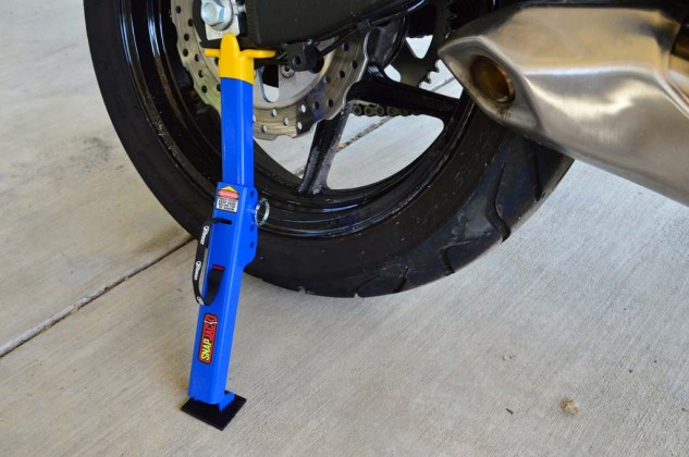 Push on the center of the SnapJack, making sure to keep fingers and skin away from the pinch point, until the unit is locked into place and the rear tire spins easily.