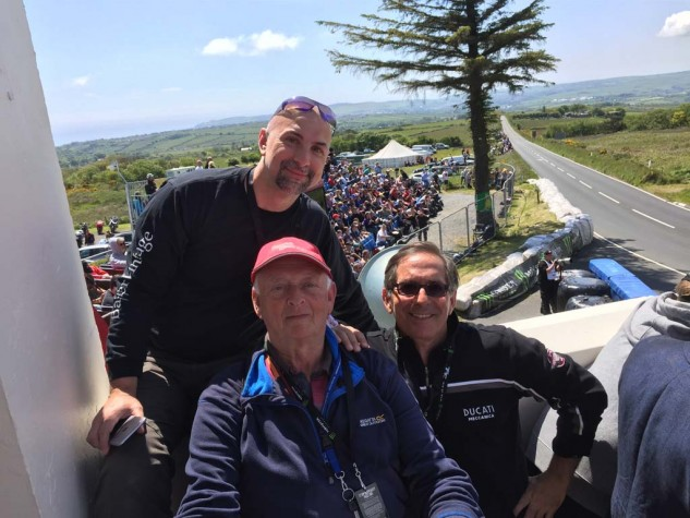 The author, Capone, with TT traveling buds John Santapietro from New Jersey, and Peter Thompson from Wales, take in the race action from the balcony of the famous Creg ny Baa.