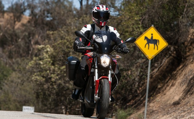 The accessory windscreen nicely diverts airflow away from the chest, up and around the rider's helmet.