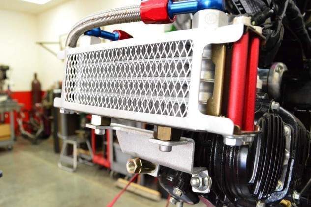 The Steady Garage oil cooler kit comes with a pre-fabricated mounting bracket that bolts to the bottom two studs. The gold collar seen in the previous picture is used to help bolt the bracket/cooler in place. The AN fitting will then thread into it.