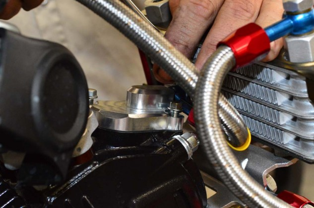The supplied billet valve cover simply bolts into place using the supplied hardware. Clearance between the radiator and AN fitting can be a little tight for a box-end wrench. Less of an issue with an open end.