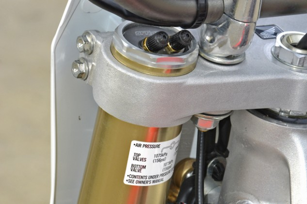 Honda revised the CRF250R's Showa SFF TAC air fork for 2016 by adding a third adjustment valve (second up top) to allow adjustment of the Outer Chamber pressure. Redesigned fork seals reduce friction as the fork goes through its stroke. The outer fork legs are also 5mm longer to allow the rider one more steering/stability adjustment by moving them up or down in the triple clamps.