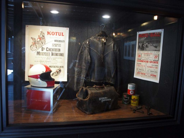 Interior window display features original gear and posters from French motorcycling events including the 1930 Motorcycle Soccer competitions.