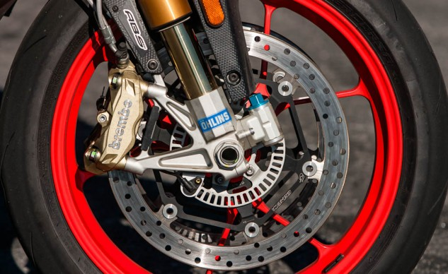 The majority of changes between the Tuono V4 1100 RR and Factory summed up in one photo. The Factory gets Öhlins suspension and steering damper, aluminum front brake rotor flanges, wider 200/55-17 rear tire, and red wheels.