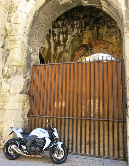 New and old. The sporty Kawasaki stands in contrast with the Roman coliseum in Arles, now an active bullfighting stadium.