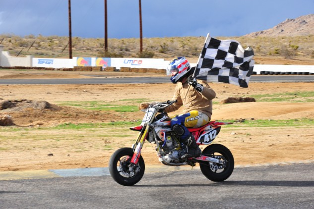 Robert Perez taking the a lap of honor with the checkered flag and the race-winning machine.
