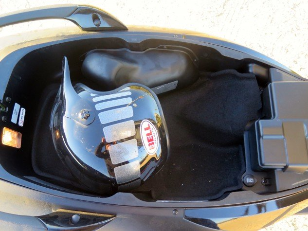 You can squeeze one full-face and one open-facer under the seat, where there's a light, a 12V outlet (180 watts) and a nice hydraulic prop to hold the seat up. The weird bulge at the top of the photo covers the emissions stuff needed for CARB compliance.