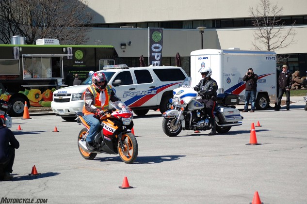 On a makeshift intersection marked by pylons, a combination of riding school Honda CBR125Rs and Harley-Davidson police bikes demonstrated slow-speed control and proper riding technique.