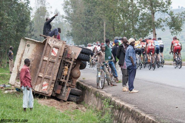 In the chaos of Rwandan traffic, a truck in the ditch is of little concern but does supply excellent seating for a passing bike race. Photo by Mjrka Boensch Bees.