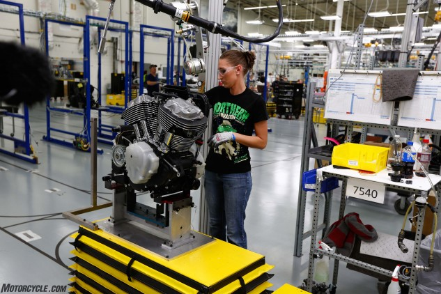 """Rosie the Riveter lives! And she has a robotic assistant, the yellow """"Smart Cart"""" system that follows a track on the floor, delivering the engines to the stations along the assembly line."""