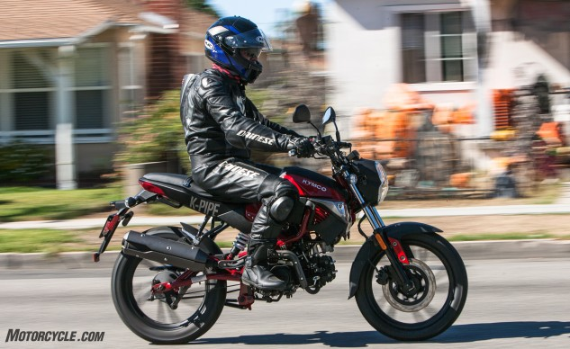The Kymco K-Pipe is in its happy place jaunting around town with a newer rider in the saddle. Leathers optional.