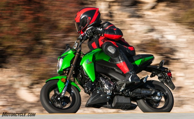 "Kevin's notes say the Kawasaki Z125 has ""Less seat-to-peg room than the others, but the most cornering clearance."" Here, Tom is graphically illustrating the seat-to-peg closeness. Check out how close his knee is to his elbow."
