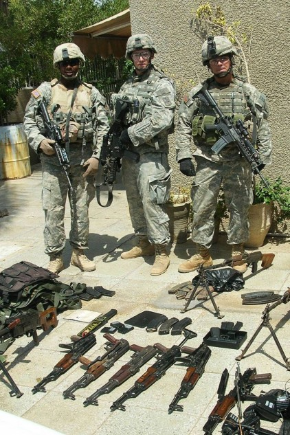 Zack, middle, with a weapons cache uncovered in Baghdad.