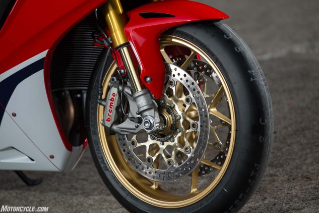 SP models get the upgraded Ohlins S-EC suspension and Brembo caliper over the standard bike's Showa BPF and Tokico caliper. Wheels are the same cast units between the two, except standard gets black, SP gold. Forged wheels are saved for the limited-edition, SP2 race homologation version. Note also the Bridgestone V02 slick tire seen here. Pay no attention to it as the SP will be sold with B-Stone's RS10 tire instead.