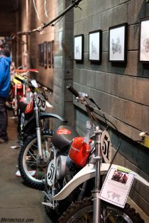 Vintage race bikes line an upstairs wall beneath art by Carter Asmann.
