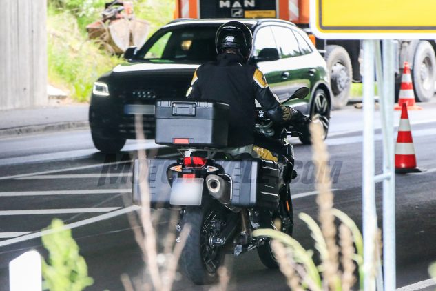 The bike in this photo differs from the other two action photos in that it has wire-spoke wheels with what appears to be an inverted fork like the bike in the static photos shot earlier.
