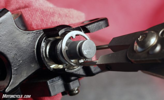 Once you have the dust cover out of the way, press the piston in slightly and remove the circlip.