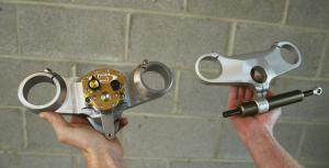 The Scotts Performance triple clamp and rotary damper (left) compared with the OEM non-adjustable Ducati parts (right).